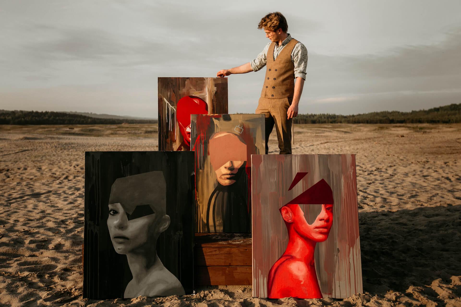 Malarz, artysta pozuję ze swoimi dziełami - Sesja biznesowa